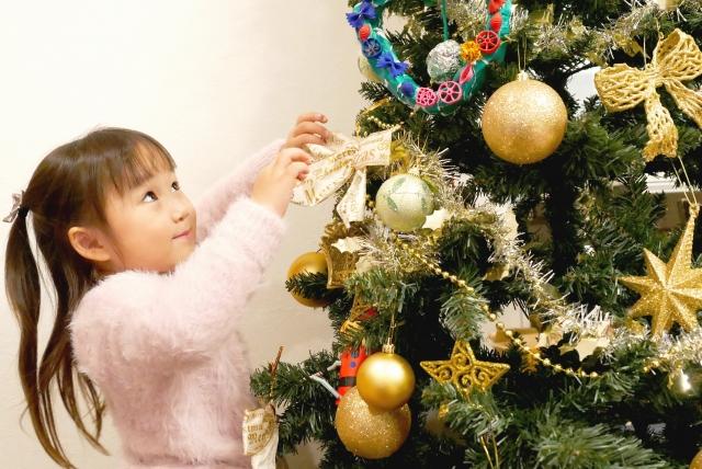 クリスマスツリーを飾り付ける子供