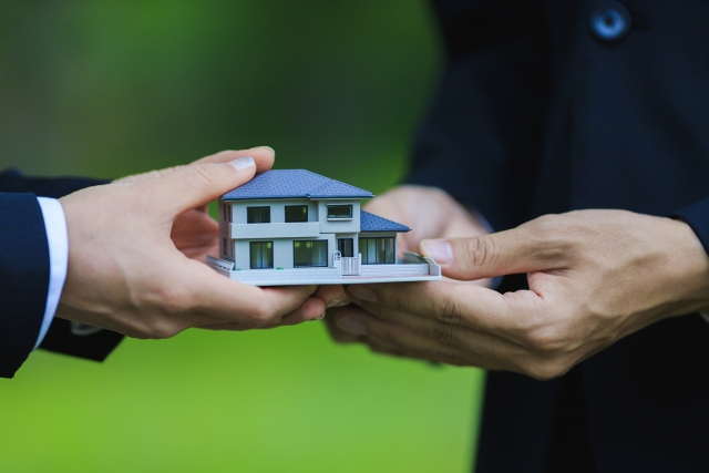 住宅の模型を手渡しする写真