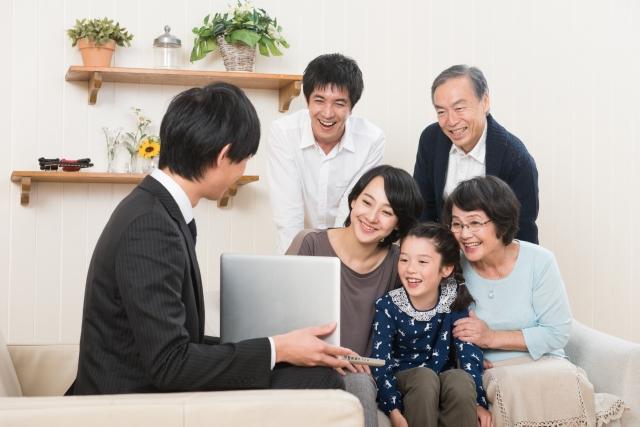 笑顔の家族が営業マンの提案を受けている画像