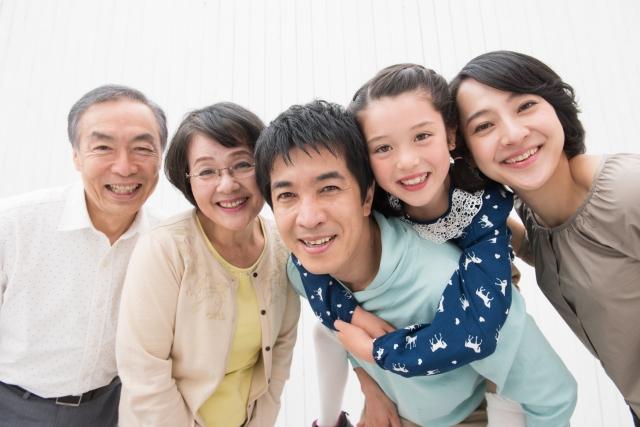 三世代の家族が集まって微笑んでいる画像