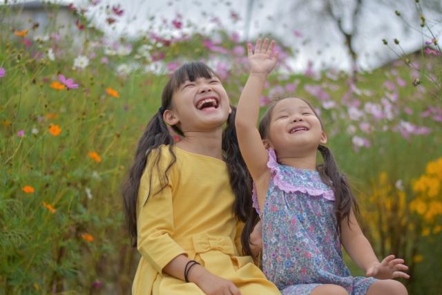 花畑で笑顔の子供の姉妹