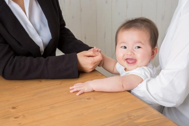 赤ちゃんと営業マンが握手している画像