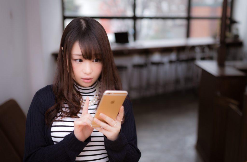 携帯を見て驚いている女性の画像